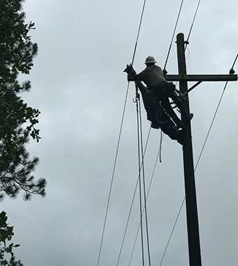 electrical work high up on a distribution power pole